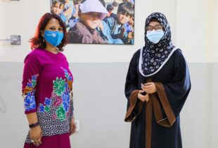 Two women wearing face masks stand by each other