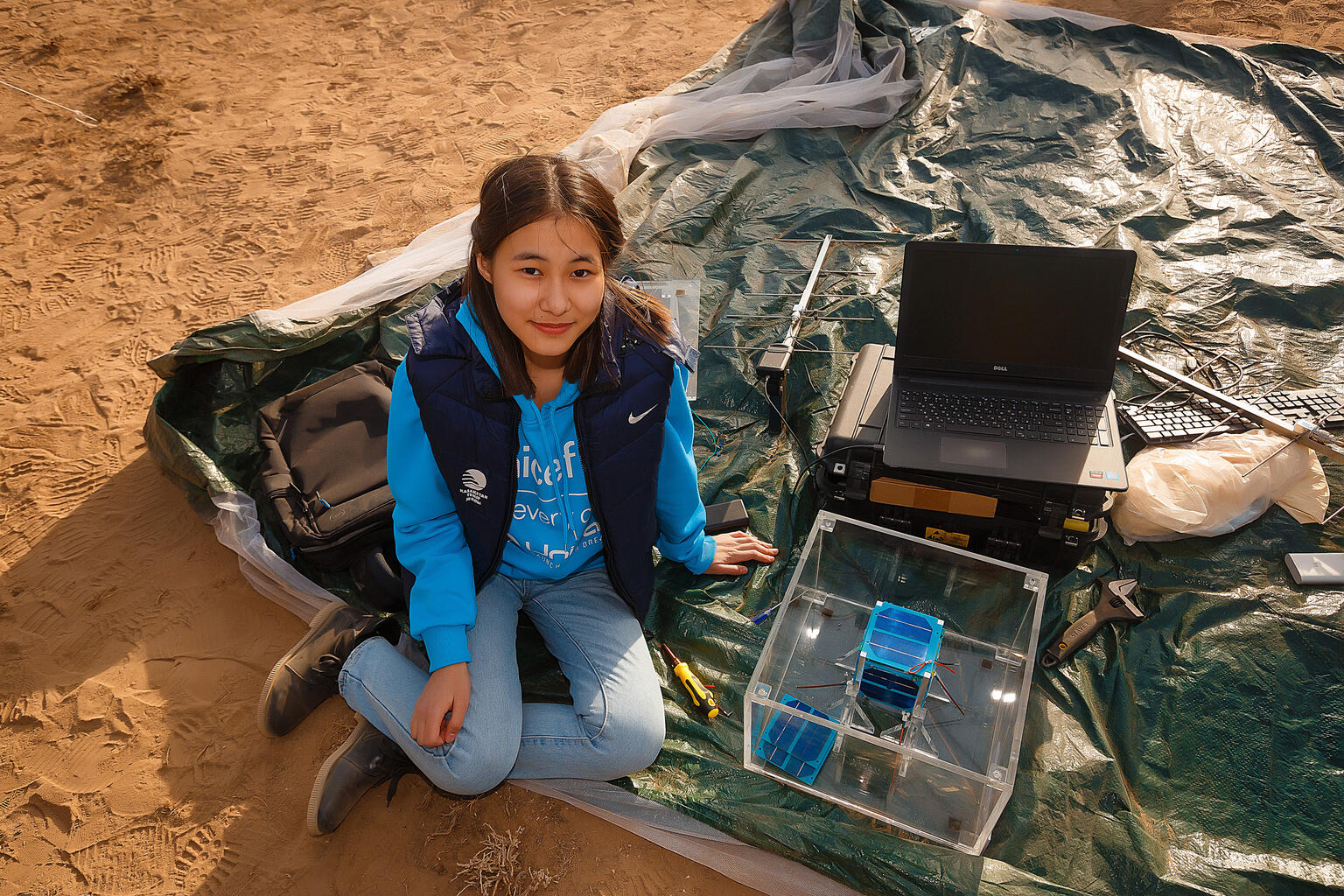 A girl sitting on the ground next to a nano-satellite looks up into the camera.