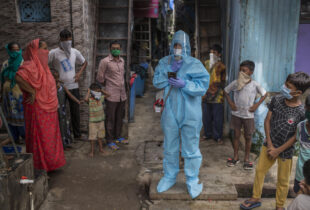 A man in PPE stands among children in a slum in Mumbai India.