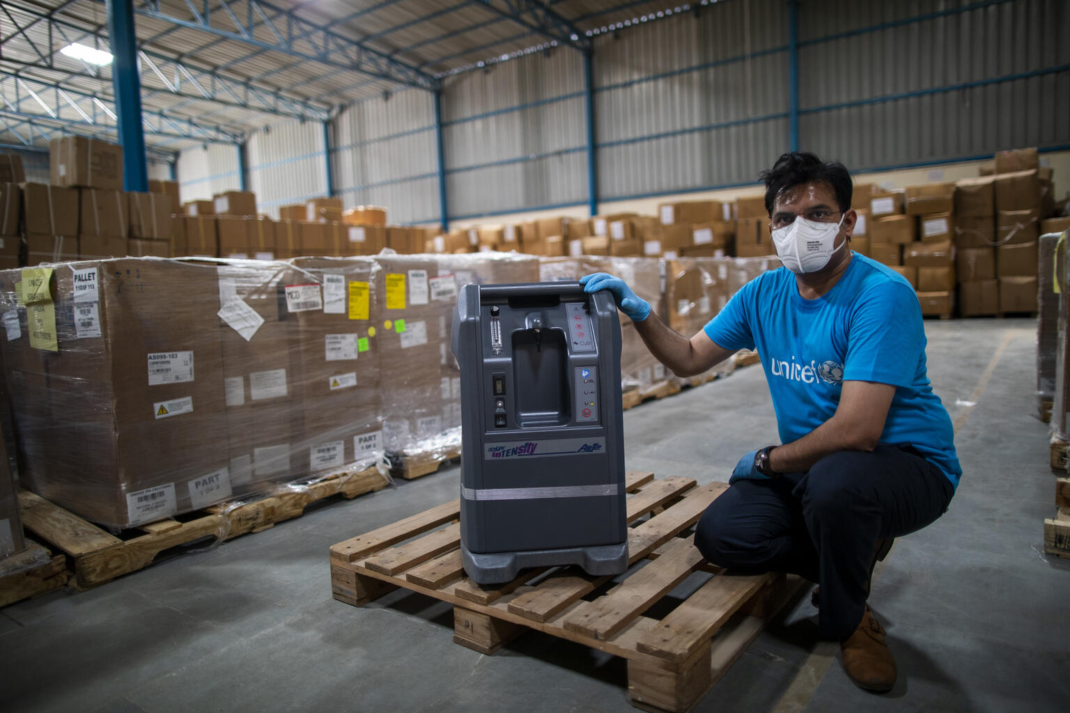 A man squats beside an oxygen concentrator in a warehouse.